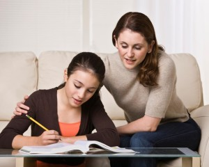 A mother is helping her young daughter with her homework.  They are looking away from the camera.  Horizontally framed shot.